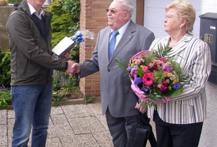 1. Vorsitzender Erik Krommus (links) überreicht das Geburtstagsgeschenk an Alfons Amfalder sowie ein Blumengebinde für seine Ehefrau Hannelore. [Foto: Björn Hackbarth]