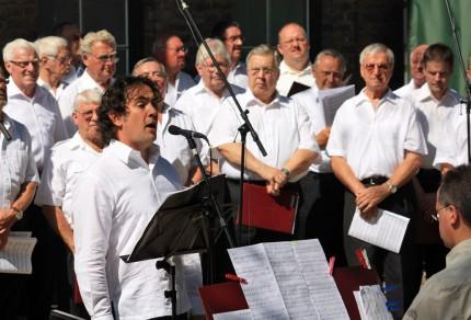 Tenor Donald Cullen unterstützte die Chorgemeinschaft mit seinen Soloparts und konnte das Publikum im Paffendorfer Schlosshof begeistern. [Foto: Bastian Schlößer]