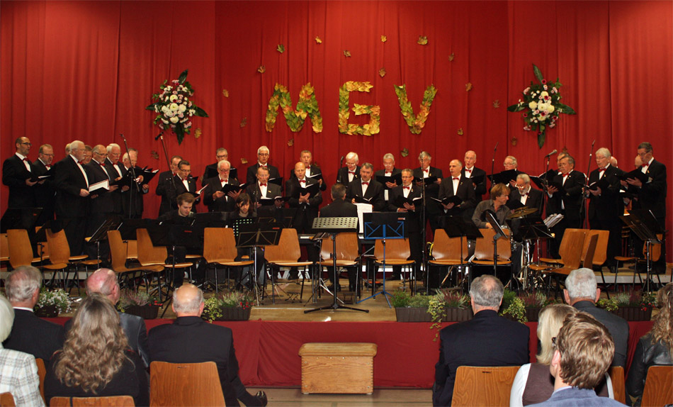 Der MGV Quartettverein 1930 Königshoven e. V. auf der herbstlich geschmückten Bühne. [Foto: Bastian Schlößer]
