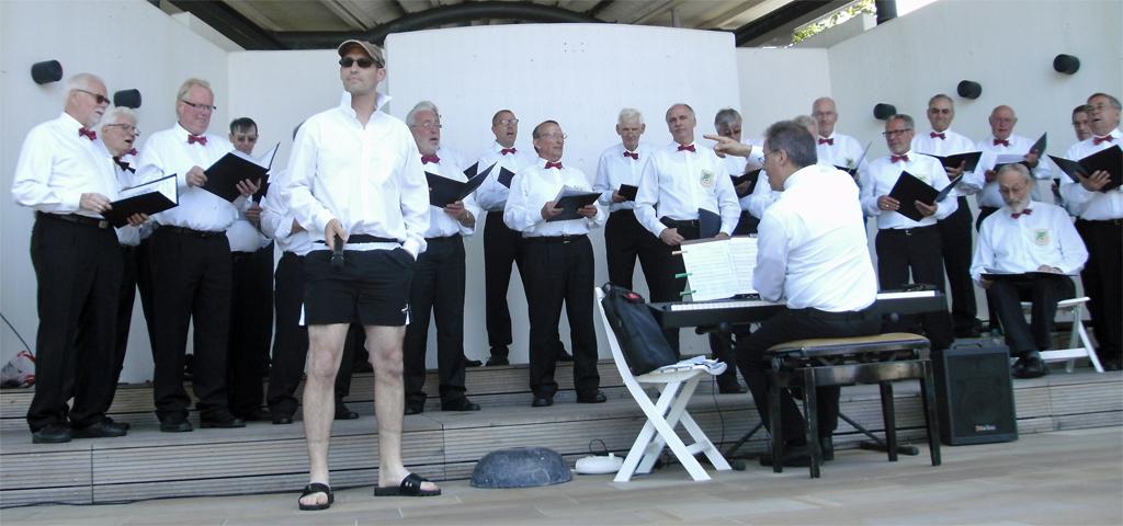 """MGV Quartettverein Königshoven mit Chorleiter Sergio Ruetsch am Keyboard und Solist Björn Hackbarth als """"Beachboy"""" (vorne) bei dem Liedvortrag """"Barbara Ann"""" von den Beachboys. [Foto: Düster]"""