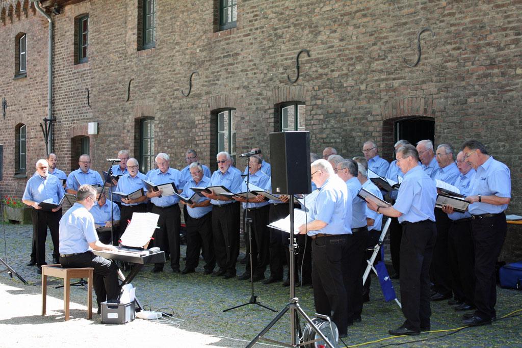 Der MGV Quartettverein 1930 Königshoven e. V. mit Chorleiter Sergio A. Ruetsch beim Sommer Open-Air-Konzert auf Schloss Paffendorf bei Bergheim. [Fotos: Bastian Schlößer]