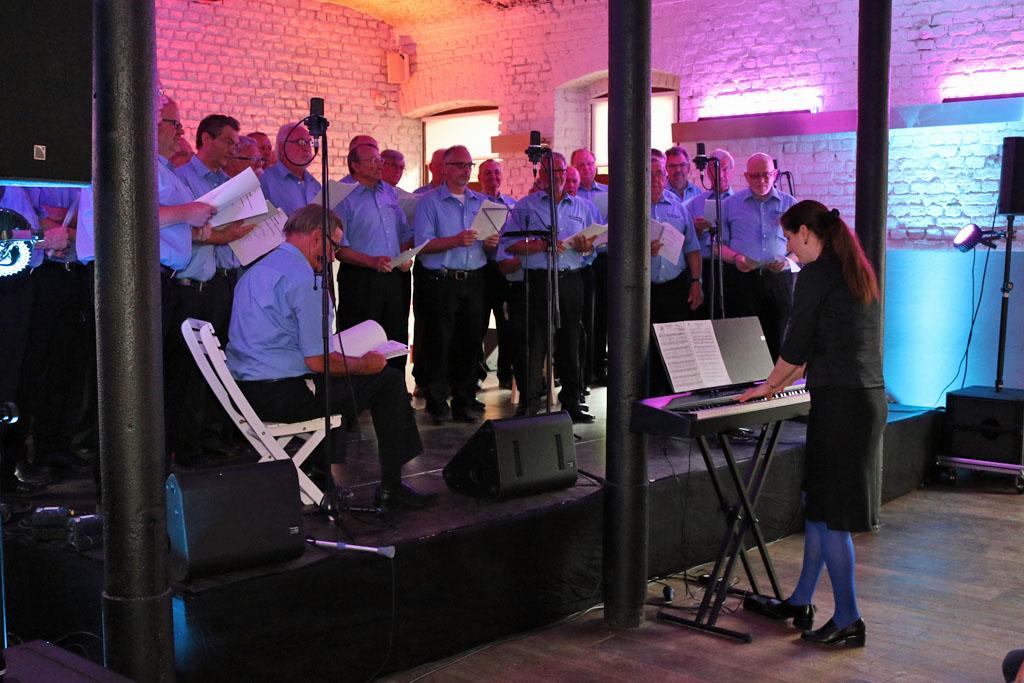 Passend zum Outfit der Königshovener Sänger, hat sich Chorleiterin Daniela Bosenius mit ihrer blauen Strumpfhose ihren Jungs in den blauen Hemden angepasst. [Fotos: Bastian Schlößer]