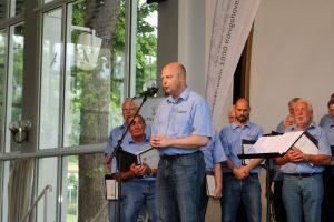 Vorsitzender Manfred Speuser begrüßte das Publikum in der Konzerthalle und stellte den Chor aus Bedburg-Königshoven vor.