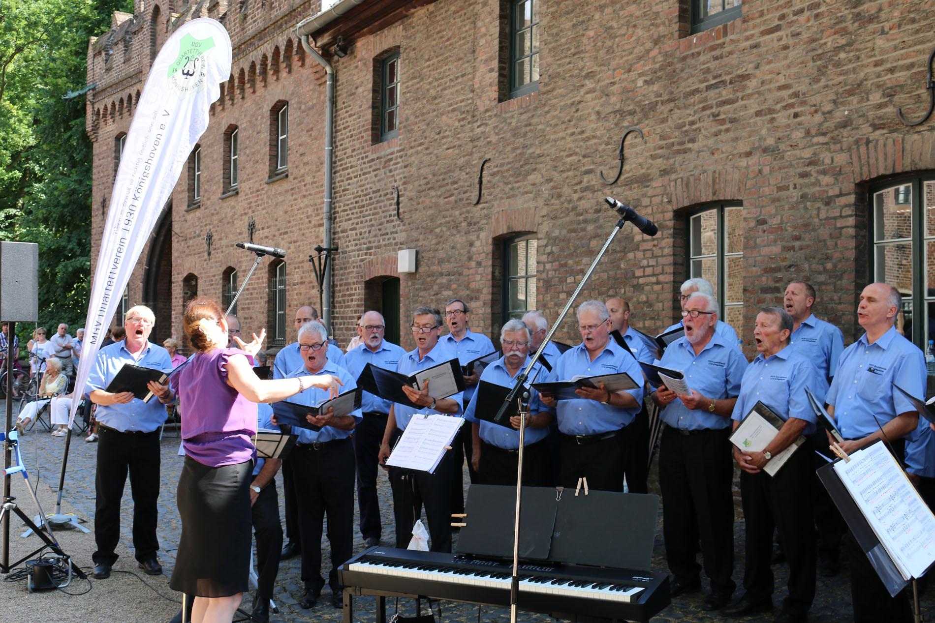 """Foto des Jahres 2017 - 1.) Chorleiterin Daniela Bosenius mit dem MGV Quartettverein 1930 Königshoven e. V. während des """"Sommer Open-Air-Konzerts 2017"""" auf Schloss Paffendorf. (Foto: Bastian Schlößer)"""
