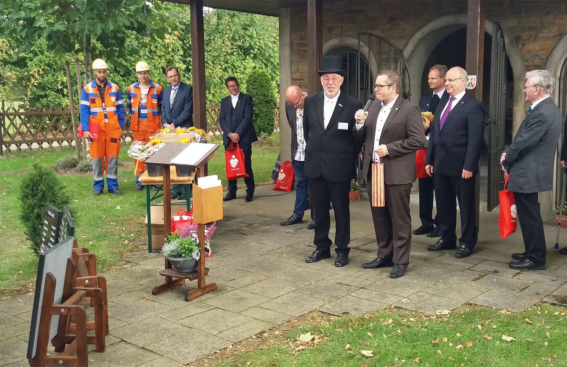 Der erste Bürger der Stadt, Sascha Solbach (rechts am Mikrofon), enthüllte u. a. gemeinsam mit dem Metallkünstler Willibert Düster (Mitte) aus Bedburg-Kaster eine Gedanktafel zur Umsiedlung ein.