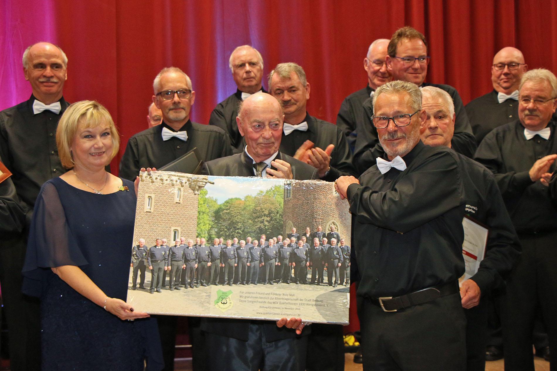 Die Überraschung mit dieser großen Fotoleinwand samt persönlicher Widmung an den neuen Ehrenbürger der Stadt Bedburg, Willy Moll, war sichtlich gelungen.